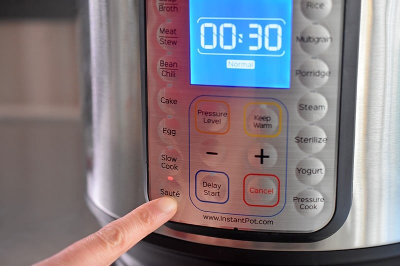 Someone pressing the Saute button on the front panel of an Instant Pot