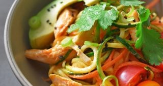 A beige bowl filled with Spicy Thai Chicken Zoodle Salad