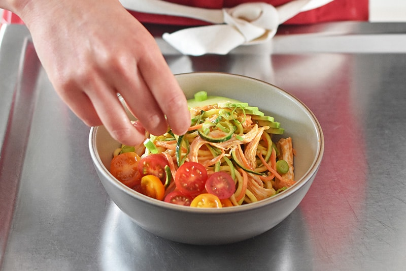 A bowl of spicy Thai chicken zoodle salad topped with tomatoes.