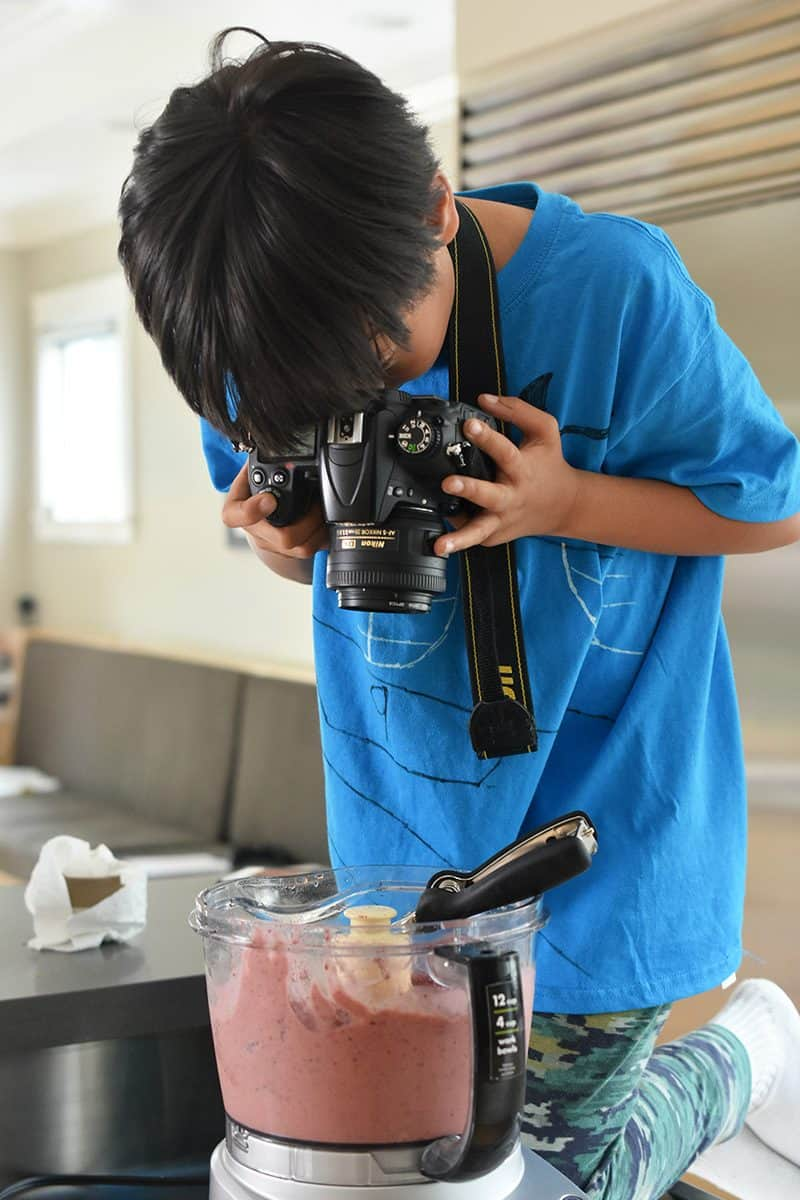 A young boy takes a picture of the strawberry banana ice cream in the food processor.