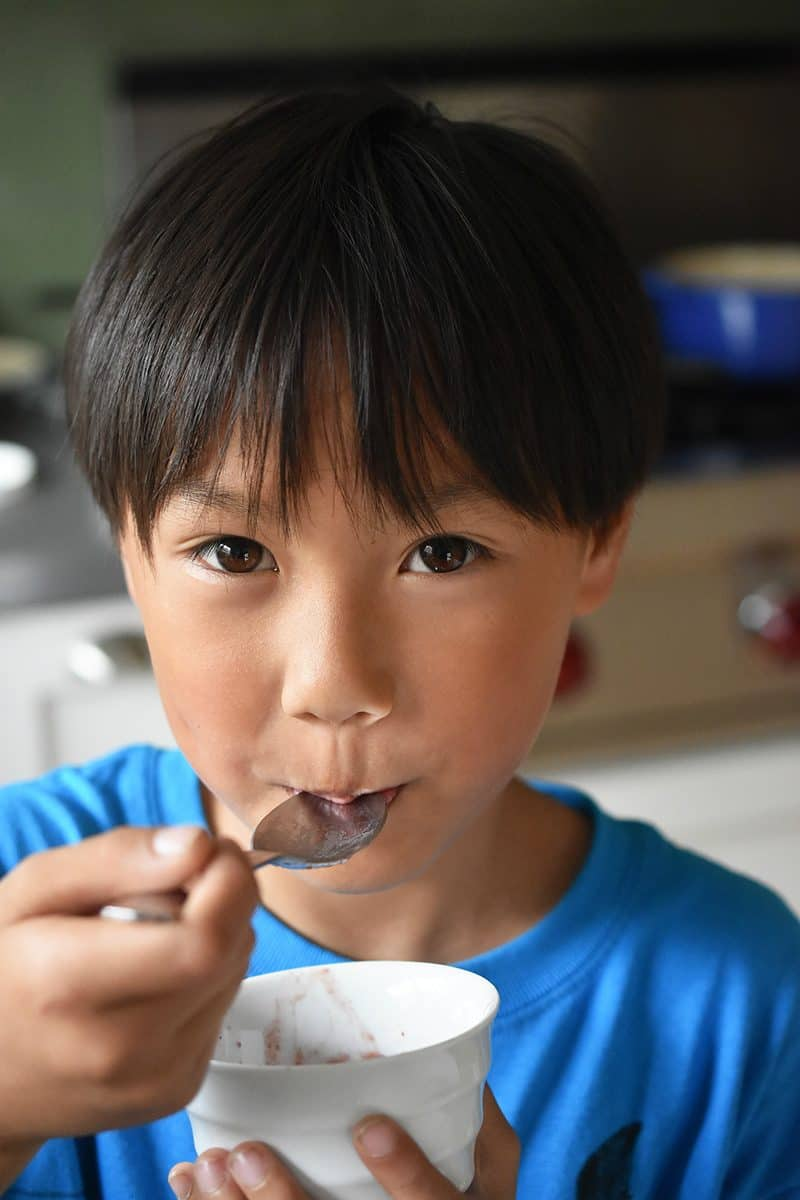 A young boy eating the dairy-free strawberry banana ice cream.