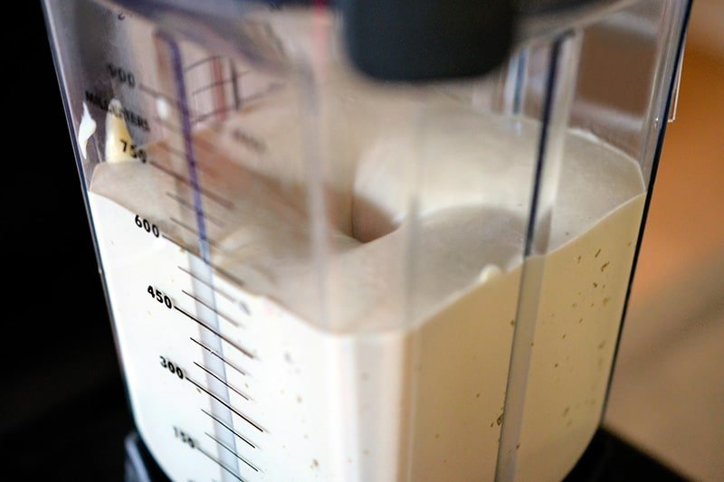 A side shot of a blender filled with creamy Tonnato Sauce