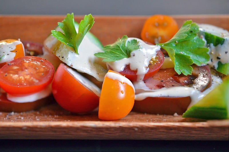 A closeup shot of a sliced tomato salad topped with creamy, Whole30 Tonnato Sauce and Italian parsley.
