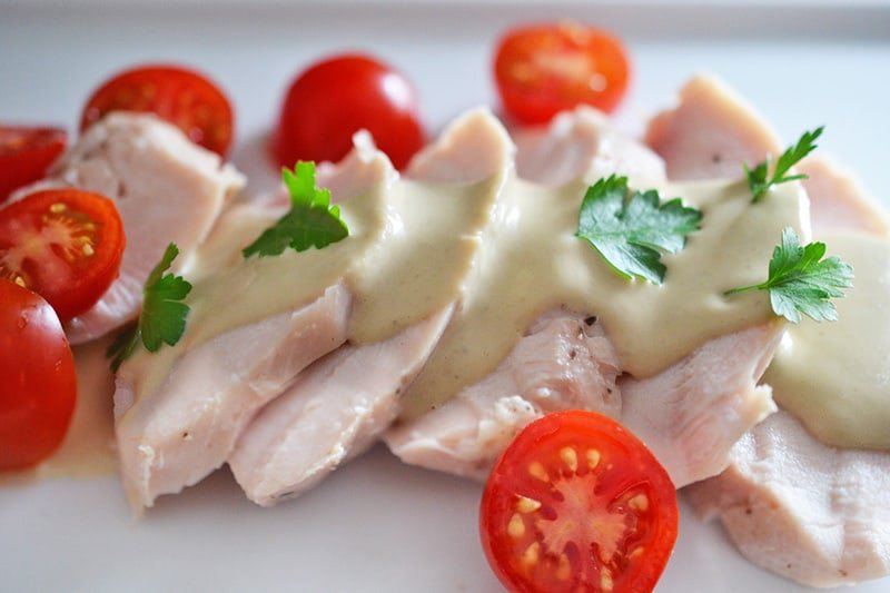 A white plate topped with poached chicken and sliced cherry tomatoes, drizzled with homemade Tonnato Sauce