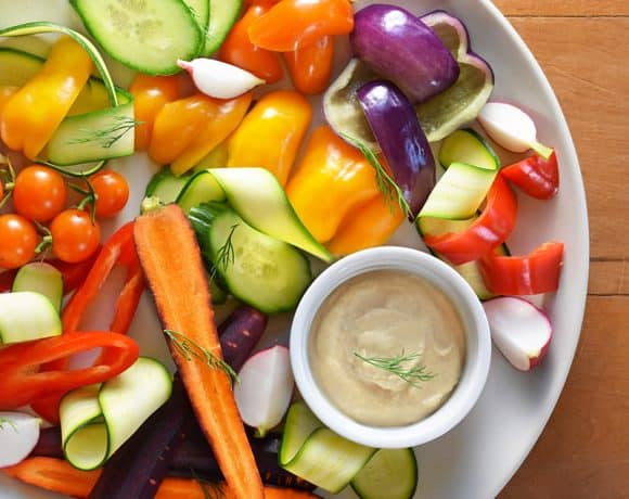 An overhead shot of a white plate filled with colorful raw vegetables and a small white ramekin filled with tonnato sauce.