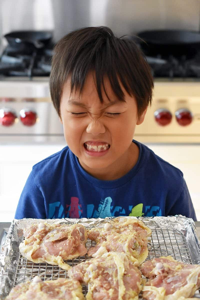 A cute kid making a funny face in front of a tray of Vietnamese Lemongrass Chicken