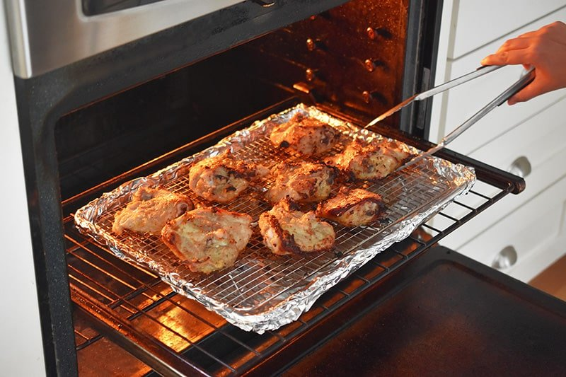 Flipping the Vietnamese Lemongrass Chicken skin side up in the oven.