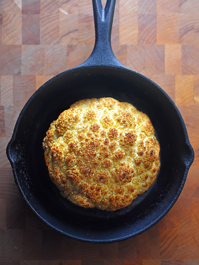 An overhead shot of Whole Roasted Cauliflower in a cast iron skillet.