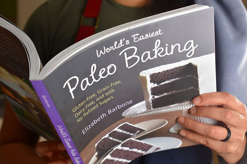 Someone reading World's Easiest Paleo Baking cookbook.