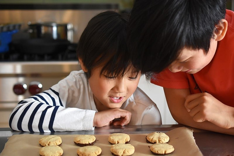 A picture of two young Asian boys staring hungrily at some freshly baked cookies.