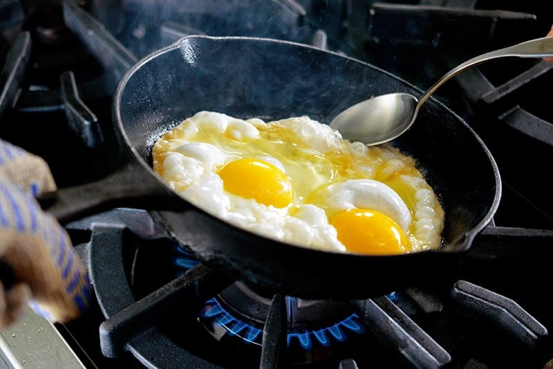 A cast iron skillet filled with two sunnyside up fried eggs is tilted with a spoon ladling hot ghee on the uncooked whites.