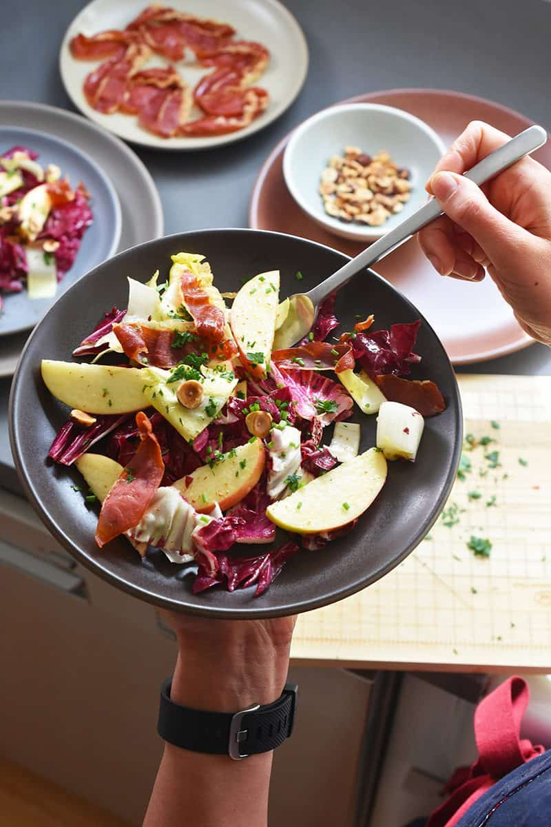 Someone holding a bowl of Endive, Radicchio, and Apple Salad with Porkitos and Hazelnuts over a cutting board.