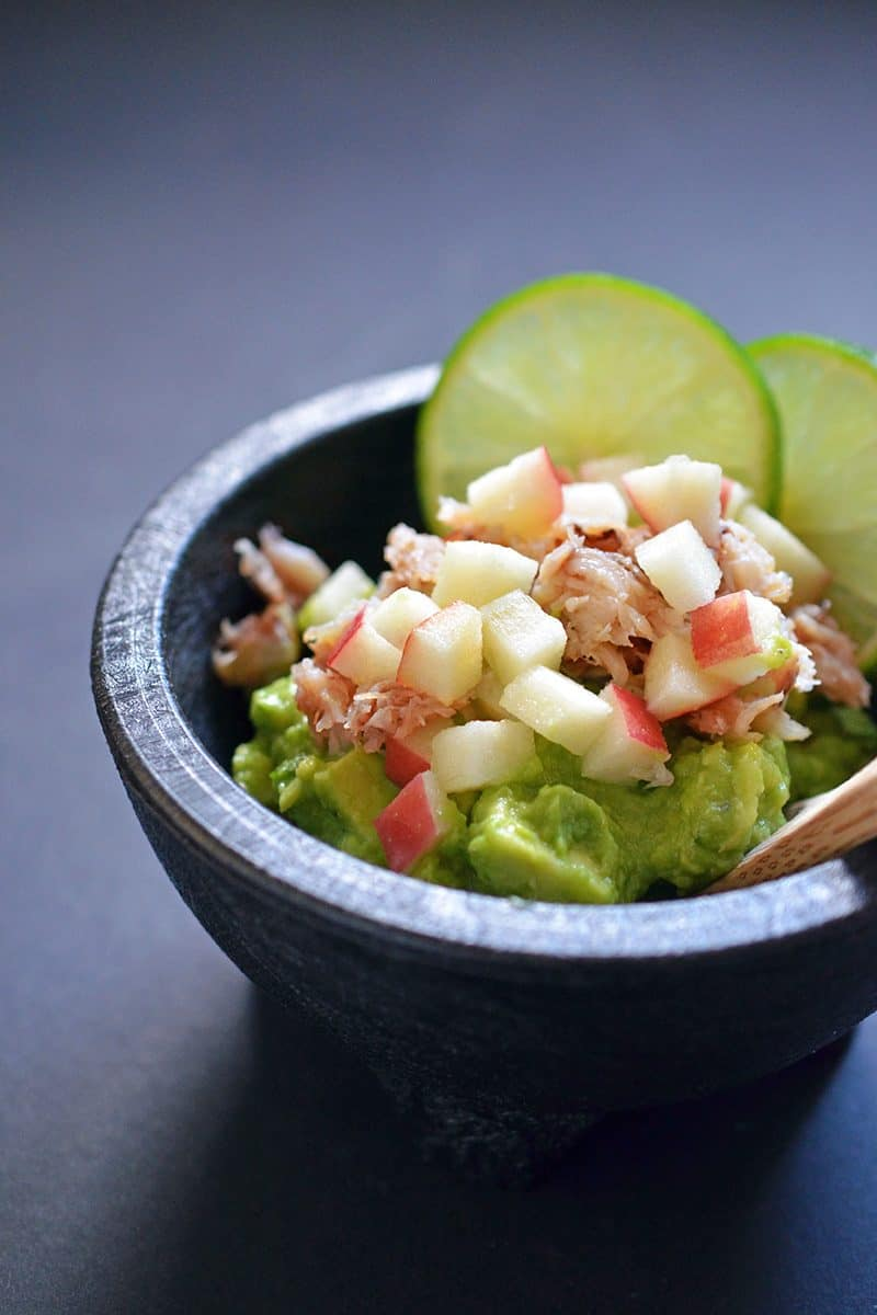 Guacamole in a black mocajete topped with lump crab meat, diced apples, and lime slices.
