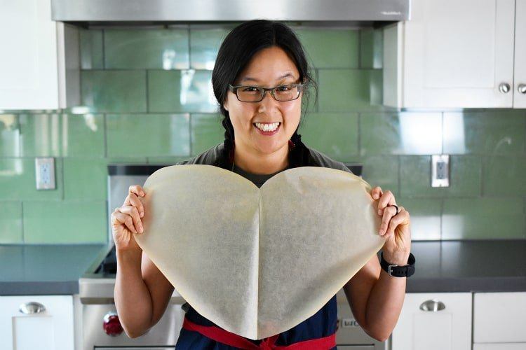 Holding up a heart shaped parchment paper to make Fiona's Phenomenal Fish Packets