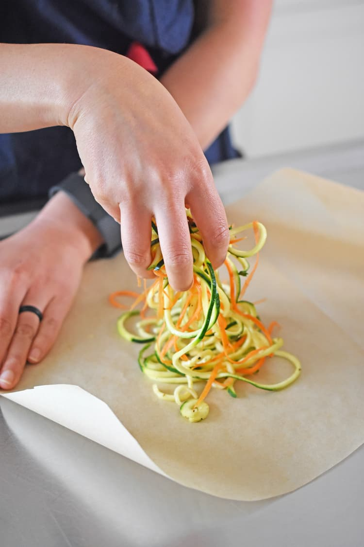 Adding seasoned spiraled vegetables to the parchment paper.