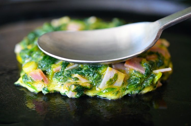 A Egg Foo Young-ish (Spinach, Egg, Ham & Coconut Pancakes) is being fried on a cast iron skillet.
