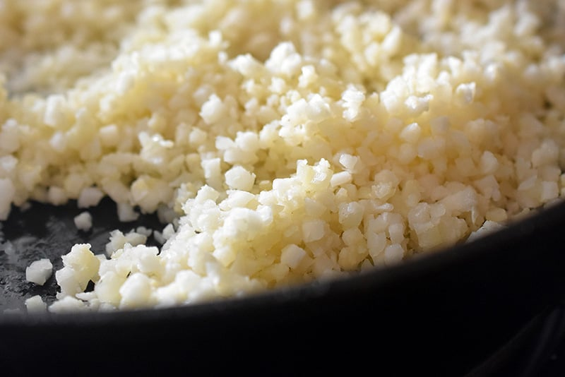 A closeup of cauliflower rice being cooked in a cast iron skillet.