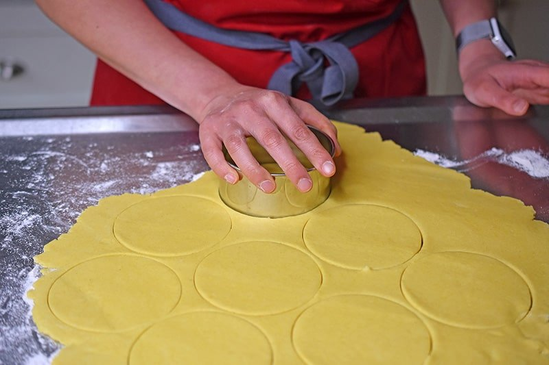 Using a biscuit cutter to cut out circles in the flattened dough