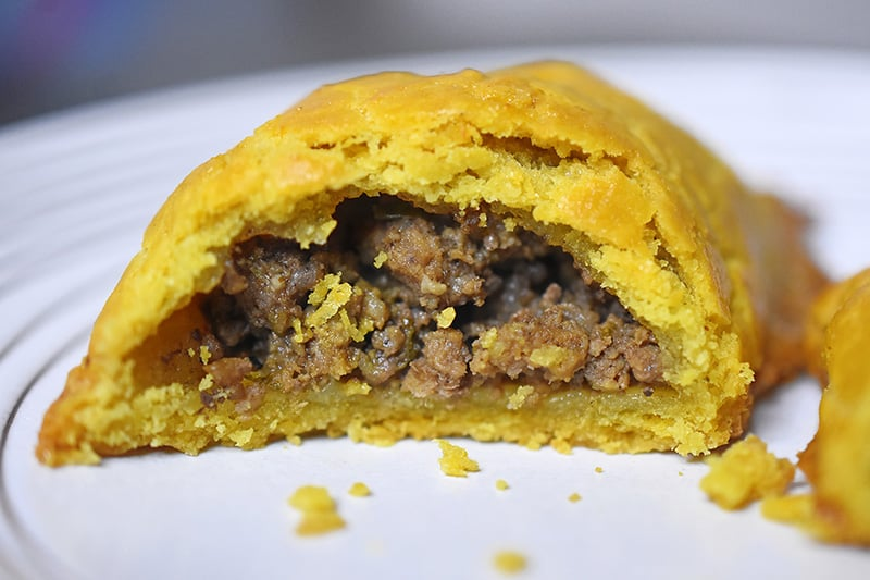 A Paleo Curried Meat Pie on a plate, cut in half.