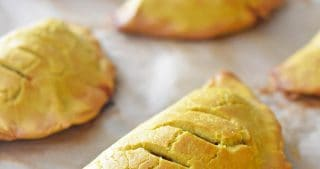 A closeup of Paleo Curried golden brown Meat Pies on a baking sheet.