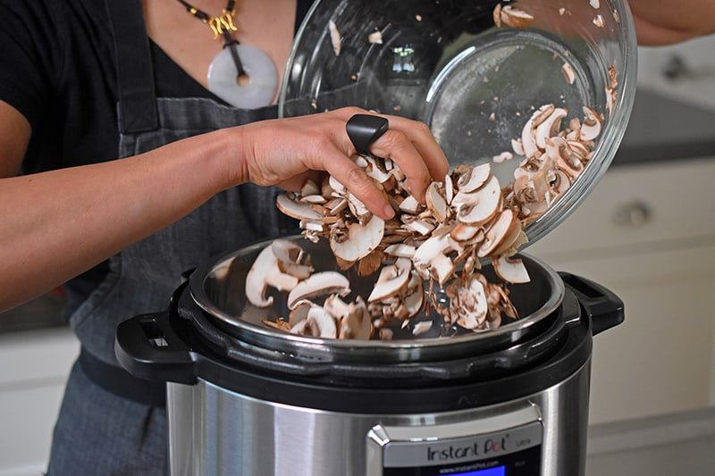 Someone dumping a bowl of chopped mushrooms into an Instant Pot.