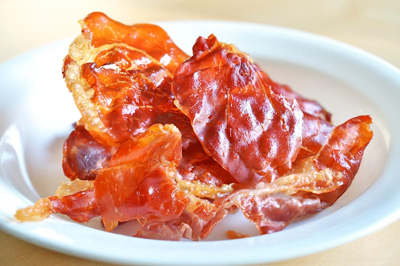 A white plate filled with Porkitos (Crispy Prosciutto Chips)
