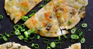 An overhead shot to two Paleo Scallion Pancakes cut into wedges and surrounded by sliced scallions.