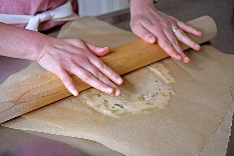 A shot of someone rolling out the Paleo Scallion pancake dough between parchment paper with a rolling pin.