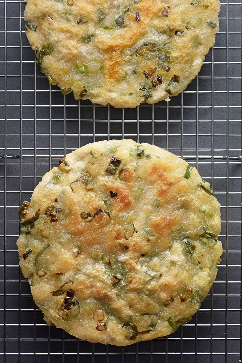 An overhead shot of two Paleo Scallion Pancakes on a wire cooling rack.