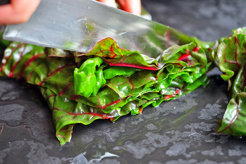 Chopping the leaves of swiss chard for a swiss chard salad.