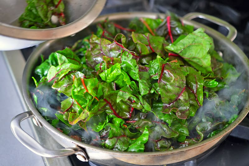 Adding the swiss chard leaves to a large hot pan for a swiss chard salad.