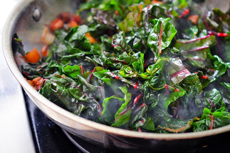 Swiss chard leaves in a pan getting cooked down.