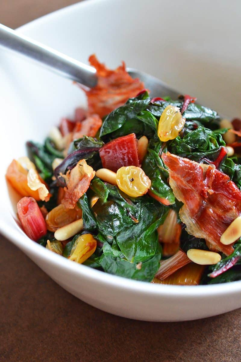 A white bowl filled with Swiss Chard with Raisins, Pine Nuts, and Porkitos