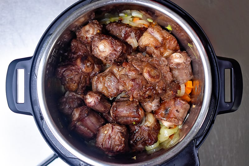 An overhead shot of Instant Pot Oxtail Stew in an open Instant Pot before it is programmed to cook under high pressure.