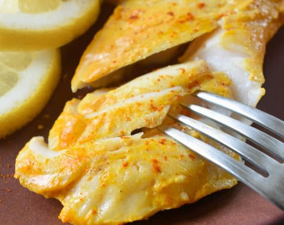 A closeup of perfectly cooked Tandoori Fish on a plate with sliced lemons.