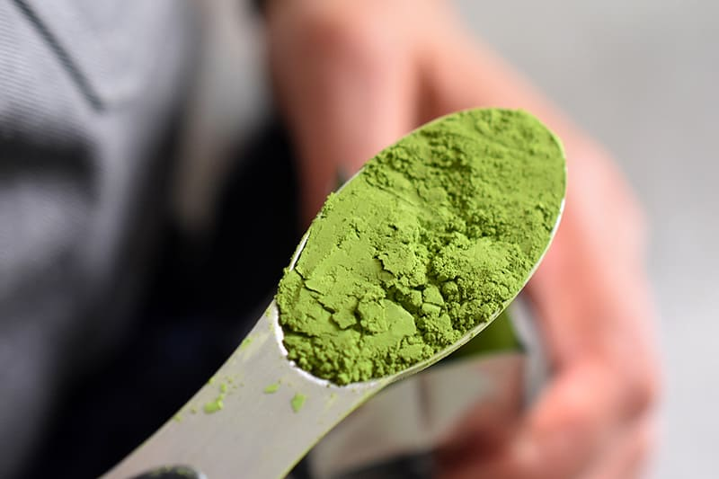 An overhead shot of a spoonful of bright green ceremonial grade matcha to make No-Bake Matcha Cheesecake