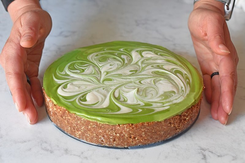 Two hands next to a healthy paleo No-Bake Matcha Cheesecake