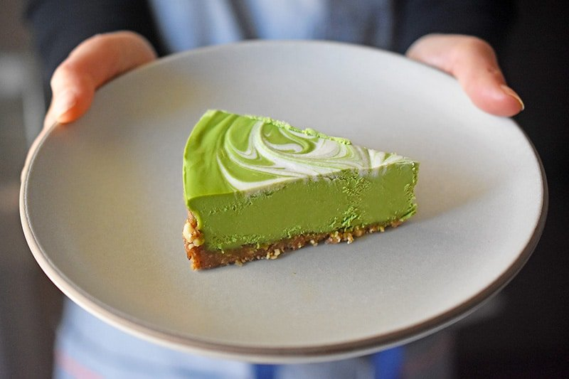 A slice of No-Bake Matcha Cheesecake on a gray plate.