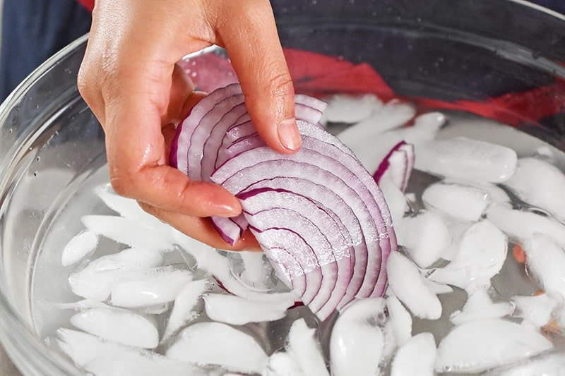 Someone soaking thinly sliced red onions in a bowl of ice water.