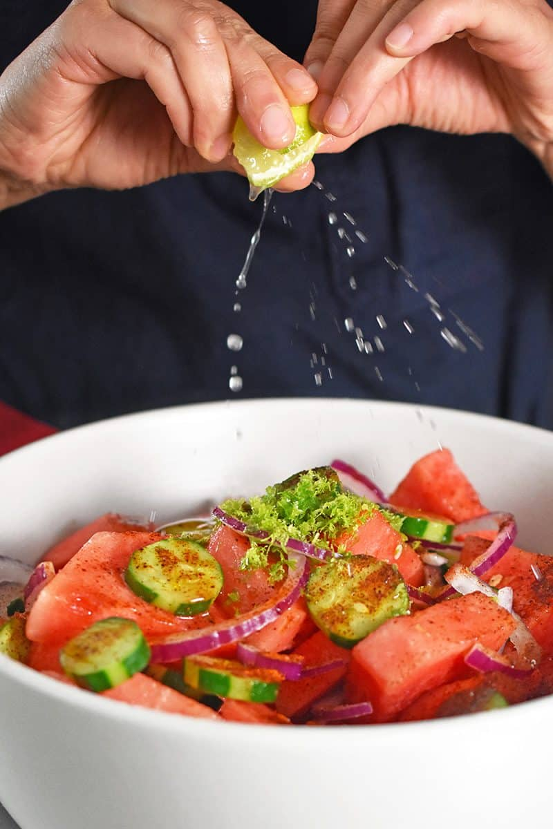 Someone spraying fresh lime juice over the paleo Mexican watermelon salad.