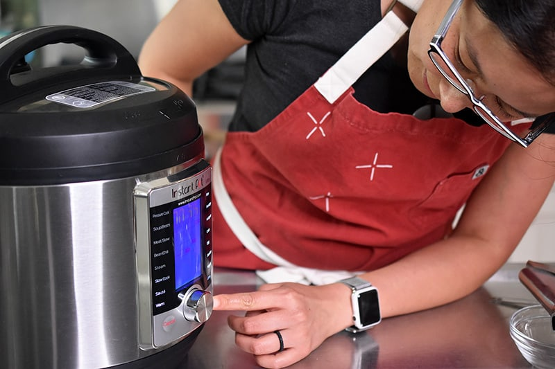 A woman leaning over to program her Instant Pot Ultra.
