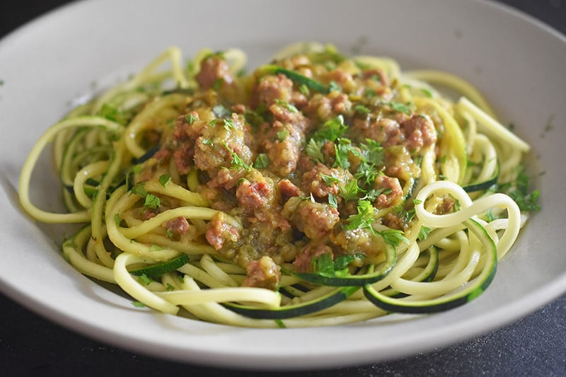 A side shot of Instant Pot Zucchini Bolognese on a bed of zucchini noodles in a shallow bowl.