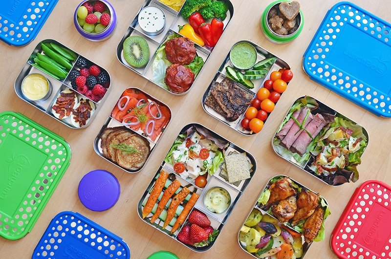 Overhead shot of a bunch of LunchBots containers filled with packed lunch ideas.
