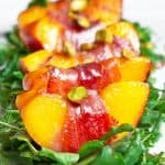 Closeup shot of watercress salad with prosciutto-wrapped peaches.