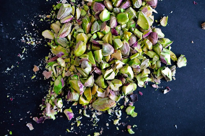 Overhead shot of crushed and chopped pistachios ready for the Watercress with Seared Prosciutto and Peaches.
