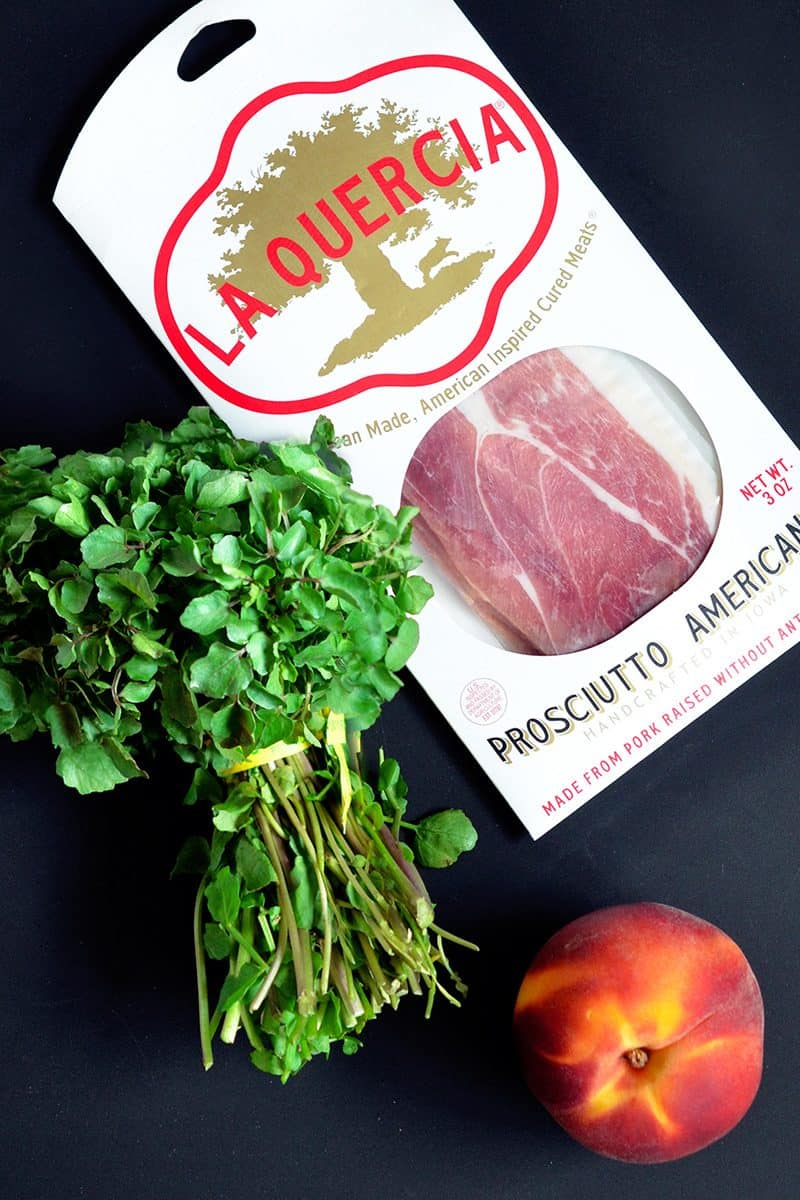 Prosciutto, watercress, and a peach sitting on a counter for the Watercress with Seared Prosciutto and Peaches recipe.