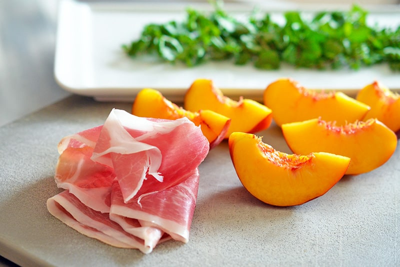 Quartered peaches, a slice of prosciutto, and washed watercress sitting on a cutting board.