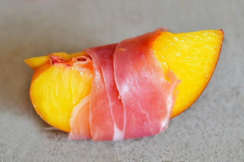 A quartered peach wrapped with a thin slice of prosciutto.
