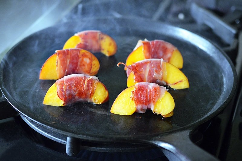Prosciutto wrapped peaches searing on a cast iron skillet.