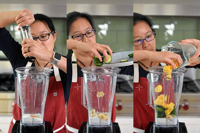 Michelle Tam adding the ingredients of freshly ground black pepper, cucumbers, and mangos for Golden Glow Smoothie into a Vitamix blender.